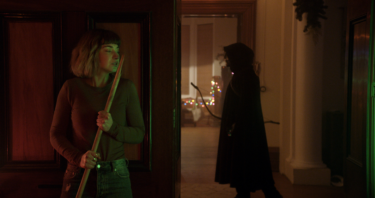 (from left) Riley (Imogen Poots) and a black-masked killer in Black Christmas, co-written and directed by Sophia Takal.